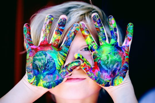 Blonde boy with colored painted hands in front of his face