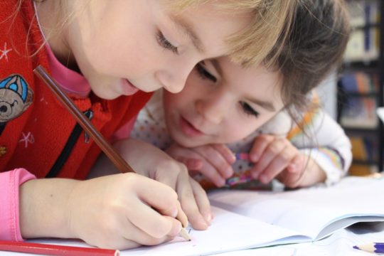 Close up photo fo two girls drawing in a notebook