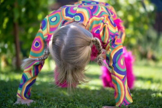 Photo of child stretching outdoors