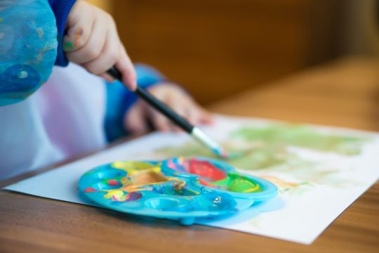 Photo of child's hands painting at a table and the paint tray
